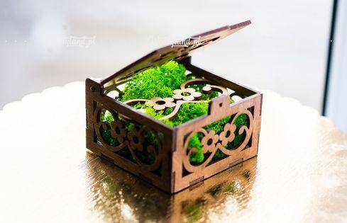 Brązowe ażurowe pudełko z mchem.